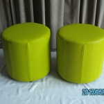 Barrel ottomans in green leather